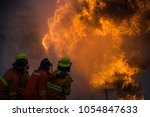 firefighters are fighting fire. | Shutterstock . vector #1054847633