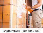 warehouse manager hand holding... | Shutterstock . vector #1054852433