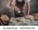 man preparing buns at table in... | Shutterstock . vector #1054946153