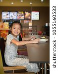 little girl have lunch at fast... | Shutterstock . vector #1055160533