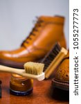 Small photo of Footwear Concepts and Ideas. Closeup of Premium Male Brogue Tanned Boots with Lots of Cleaning Accessories on Foreground.Vertical Image