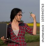 Small photo of Pretty young woman agronomist checking sprouts in field. Plant protection and agribusiness concept