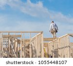 rear view roofer builder on... | Shutterstock . vector #1055448107