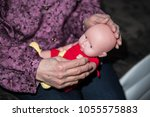 old woman holding a baby | Shutterstock . vector #1055575883