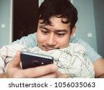 asian man using his smartphone... | Shutterstock . vector #1056035063