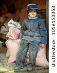 Small photo of Happy child son of farmer sitting on bags with mixed fodder for pigs