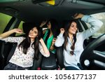 three girls driving in a car... | Shutterstock . vector #1056177137