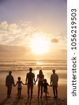 Small photo of Rear View Of Multi Generation Family Silhouetted On Beach