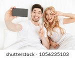 Small photo of Image of cheerful young loving couple make selfie by by mobile phone in bed with peace gesture.