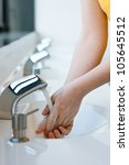 Washing hands in a public restroom (selective focus) - stock photo