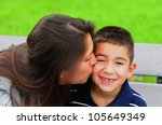 Loving mother kissing her attractive young son on the cheek - stock photo