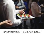 waiter carrying trays with food.... | Shutterstock . vector #1057341263