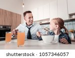 Small photo of Lets talk. Joyful girl sitting near her father and turning head while being in all ears