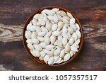 bowl with white pumpkin seeds... | Shutterstock . vector #1057357517