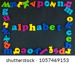 Small photo of Alphabet written. Frame of plastic alphabetical letters on the black leather background.