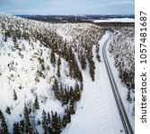Small photo of Aerial view of a winter road. Winter landscape countryside. Aerial photography of snow forest. Captured from above with a drone. Aerial photography