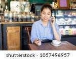 cheerful asian woman calling... | Shutterstock . vector #1057496957