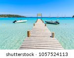 wooden jetty with boats on... | Shutterstock . vector #1057524113