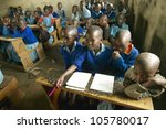 JANUARY 2005 - Children in blue uniforms at school behind desk near Tsavo National Park, Kenya, Africa - stock photo