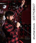 Small photo of Man with enthusiastic face holds microphone, singing song, karaoke club background. Music and leisure concept. Musician with beard and mustache singing song in karaoke. Hipster likes to sing on stage.