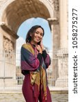 Small photo of Vertical picture of long hair woman smiling in front of the The Arch of Constantine during sunny day in Italy