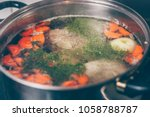 cook cooks broth in a saucepan...   Shutterstock . vector #1058788787