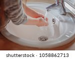 little girl washes her hands in ... | Shutterstock . vector #1058862713