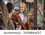 Small photo of Happy together. Charming female person sitting on the bench near her friend, expressing positivity while being in all ears