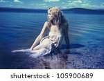 Young sexy blond woman in the blue water in wet white dress - stock photo