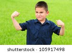 Young boy who is flexing his muscles with a mean face - stock photo