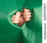 Small photo of A man looks through a hole in a green paper background. peep. Curiosity.