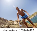 Small photo of Young adventuristic muscular bearded man tourist taking a selfie with a stick while standing on the stone beach.
