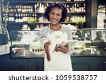 Small photo of Smiling young African cafe owner extending a handshake while standing in a trendy cafe holding a digital tablet