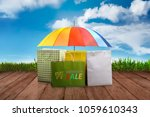 Small photo of Colorful shopping bag and umbrella on wooden plank at Monsoon sale. Monsoon sale concept