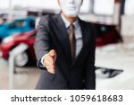 Small photo of Dishonest and evil salesman in business suit in car dealership company handshaking welcome customers to exploit and deceive customers - fraud and bad quality service in business concept