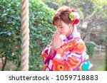 Stock photo attractive asian woman wearing japanese kimono praying at a shinto shrine 1059718883