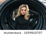 Small photo of very beautiful girl on the background of a tunnel of pipes gazing intently and enchantingly with her gaze