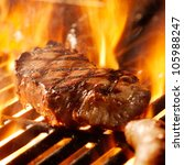 beef steak on the grill with flames. - stock photo
