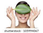 smiling female hiding behind green leaf - stock photo