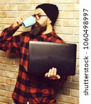 Small photo of Bearded man, long beard. Brutal caucasian serious unshaven hipster holding laptop drink from mag or cup in red black checkered shirt with hat and glasses on beige brick wall studio background