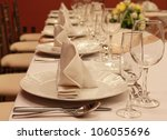 Glasses and plates on table in restaurant background - stock photo