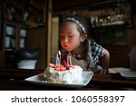 little girl blowing out the... | Shutterstock . vector #1060558397