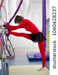Small photo of Flexible woman gymnast stretching at the barre in a studio