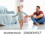 baby taking first steps with... | Shutterstock . vector #1060654517