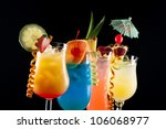 Tequila Sunrise, Blue Lagoon, Rum Runner, and Bahama Mama cocktails over black background on reflection surface - stock photo