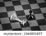 Small photo of The winner is the pawn and the defeated king on the chessboard. Chess. Competition and victory concept. Black and white photography