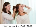 Sisters having an argument and getting physical with a fight. - stock photo