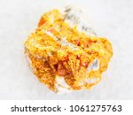 Small photo of macro shooting of natural mineral rock specimen - rough yellow Orpiment crystals on white dolomite stone on white marble background from Kabardino-Balkarian Republic, Northern Caucasus Region, Russia