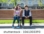 Small photo of Boy and girl teenagers play, read, look at the smartphone. On the bench, the urban background. Rest, vacations, lifestyle of adolescent children