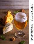 Small photo of Beer and cheese. Beer glass on wooden table. Ale and appetizer snack. vertical